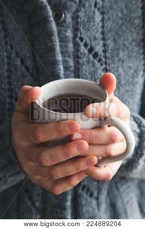 Woman wearing a gray woolly cardigan holding a mug of tea