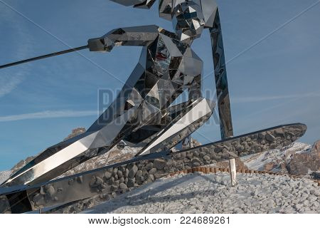 Bolzano, Italy - february 2015:Silver Skier Statue, Sculpture Made with Mirrors and Italian Dolomites Alps in background