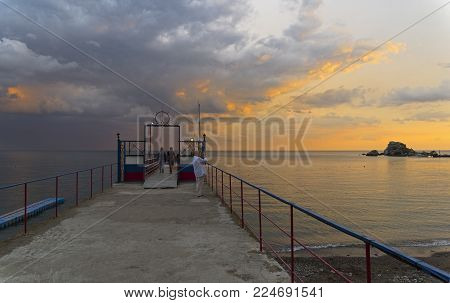 SUDAK, CRIMEA - September 6, 2017: Evening sky over the Black Sea. View from the pier of the resort town of Sudak, Crimea.