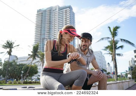 Couple of joggers in Miami checking running time