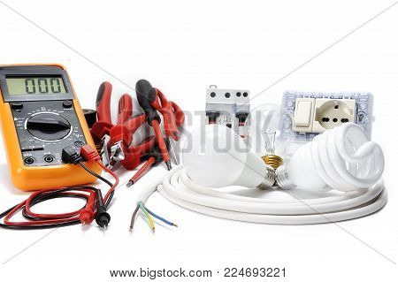 Multimeter, work tools and components for a residential electrical installation, photographed on a white background.