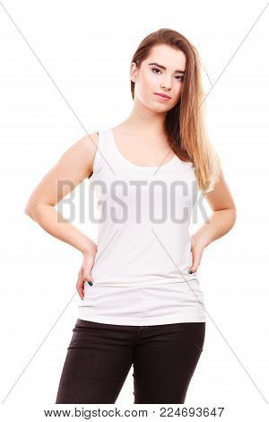 Teenage beauty concept. Portrait of young teenager woman with long brown having neutral face expression, wearing white tank top and black leggings
