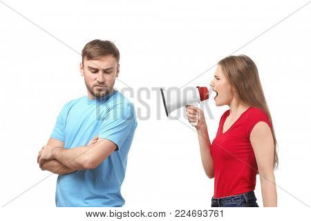 Young woman shouting into megaphone at man on white background. Problems in relationship