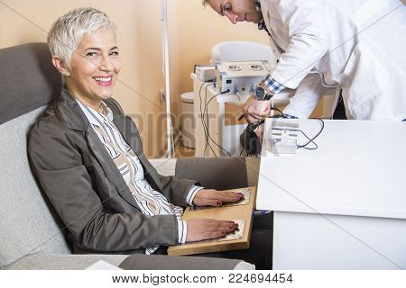 Senior woman checking her health status at the clinic, undergoing quantum and bioresonant medical exam