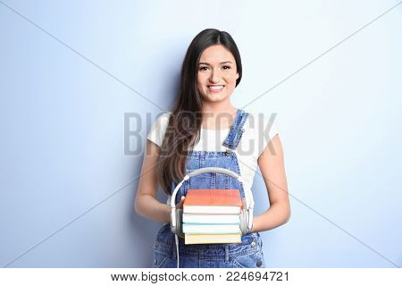 Woman with literature and headphones on color background. Listening to audiobook