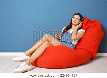Woman listening to audiobook through headphones near color wall