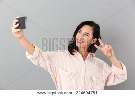 Portrait of a happy businesswoman taking a selfie isolated over gray background