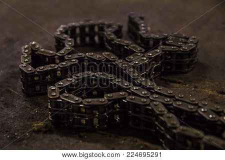 Used sprocket rear chain for ATV, off-road, motobike wheel laying on a repair bench in a repair shop