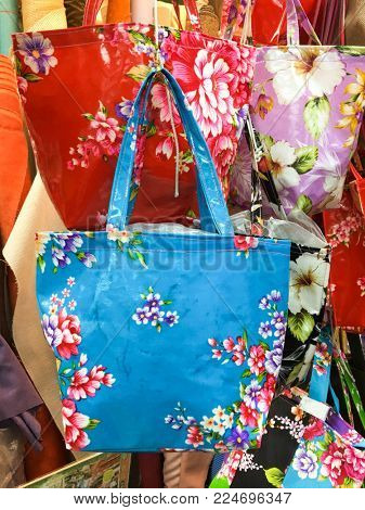 Various many coloured floral bags on hanging , with clipping path