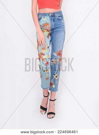 Front view Fashion. Woman legs in embroidered flowers, jeans and high heels shoes posing