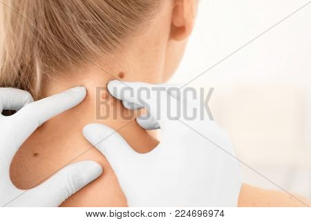 Oncologist examining female patient in clinic. Cancer awareness poster