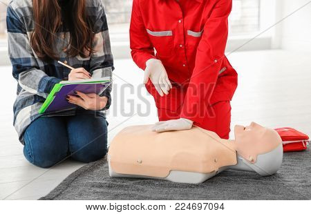 Woman demonstrating CPR on mannequin in first aid class