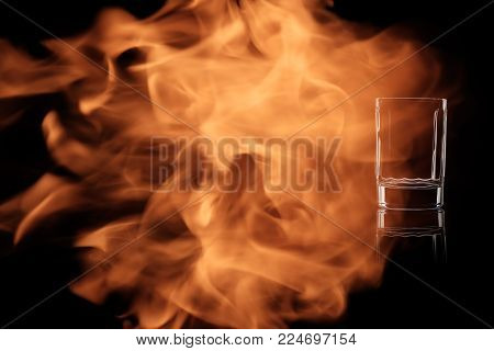 A small shot of vodka or tequila isolated on black background in the fire flames.