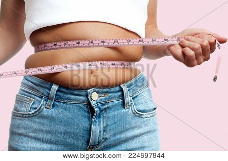 Overweight woman with tape measure around waist on pastel pink background