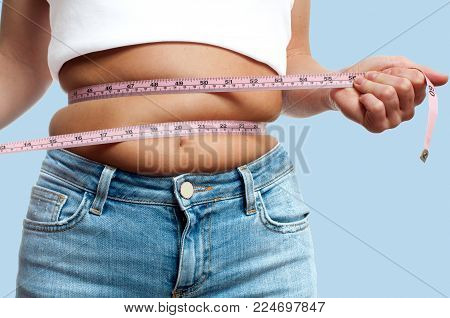 Overweight woman with tape measure around waist on pastel blue background