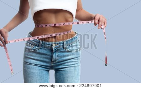 Diet concept. Woman is measuring waist after weight loss on pastel background