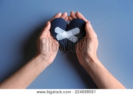 Woman holding torn paper heart with medical patches on grey background. Relationship problems
