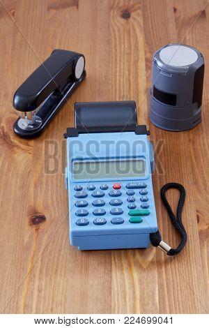Mobile cash register, ofice stamp for documents and stapler on desk.