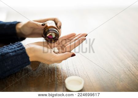 Close up of female hands taking out medicine pill from bottle into her hand on wooden table