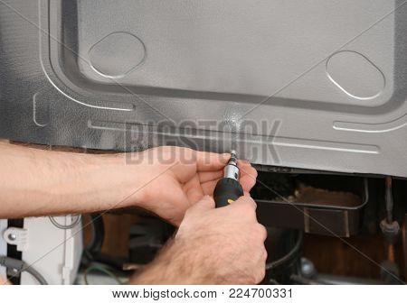 Male technician repairing refrigerator, closeup