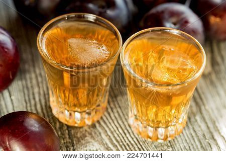 Plum liqueur or slivovitz, plum rakia with fresh and tasty plum on rustic wooden background