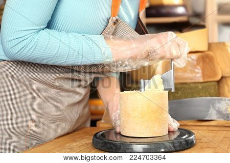 Young woman scraping delicious cheese with girolle in shop