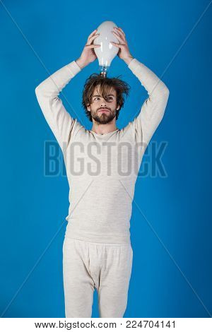 Energy and electricity concept. guy has an idea on blue background, morning. Power and business success. Solution and decision. Man with disheveled hair hold big lamp.