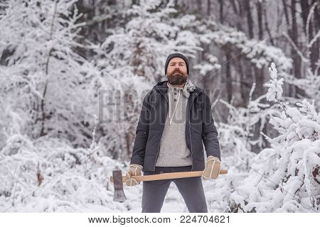 Bearded Man With Axe In Snowy Forest. Temperature, Freezing, Cold Snap, Snowfall. Skincare And Beard