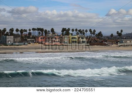 Large waves breaking on the beach in front of seaside cottages and houses in Imperial Beach, San Diego, California, as seen from the community pier.