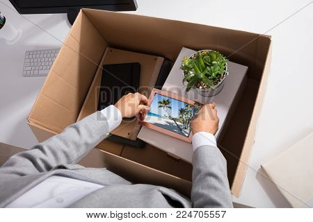 Close-up Of A Businesswoman Packing Picture Frame In Cardboard Box At Workplace