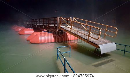 Wooden massive floating pontoon bridge with red floats surrounded with fog at night during flood, completely risen from concrete pier and metal handrail