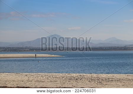 San Diego, California, USA - January 25, 2018 - A sole fisherman standing on a white sand spit trolls the blue waters of San Diego Bay with Mt. Miguel in the distance at the Silver Strand State Beach.