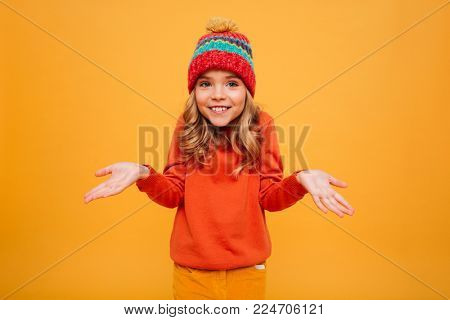 Smiling Young girl in sweater and hat shrugs her shoulders and looking at the camera over orange background