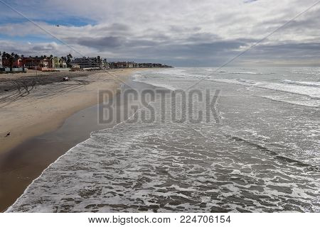 View down the beautiful wide sandy beach at  Imperial Beach, San Diego, California as waves leave foamy water on the shore, and the wet sand reflects a cloudy sky.
