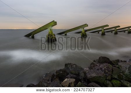 Icebreakers on the shore of Marken. The wooden structures were built in 1872 to provide protection from ice formations in the IJsselmeer lake. Long exposure nightscape in moonlight.