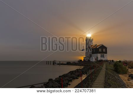 Lighthouse called The Horse of Marken illuminates a colorful sky over the IJsselmeer lake, The Netherlands. Long exposure nightscape in moonlight.