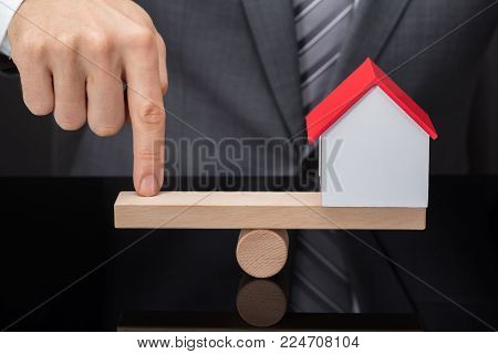 Close-up Of A Person's Finger Balancing House Model On Wooden Seesaw