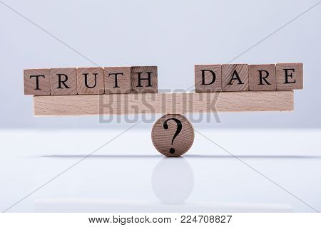 Truth And Dare Arranged Blocks Are Balanced On The Wooden Seesaw With Question Mark