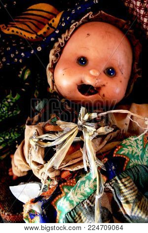 Creepy abandoned child's doll with dirt and decay