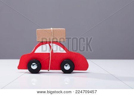 Red Car Transporting Cardboard Box Against Grey Background