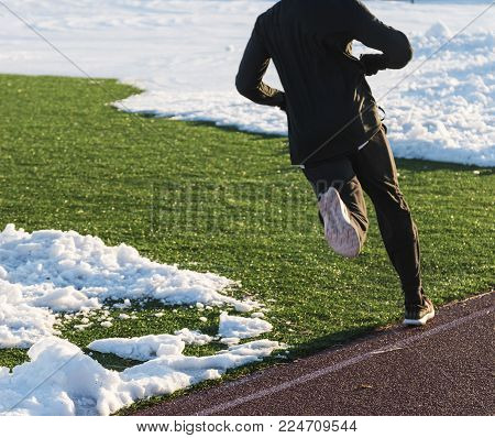 High school track runner dressed all in black, rus a workout on the track and on the field around the snow.