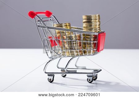 Close-up Of Shopping Cart Filled With Stacked Golden Coins