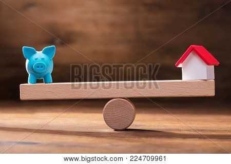 Balancing Of Blue Piggybank And Miniature House Model On The Wooden Seesaw