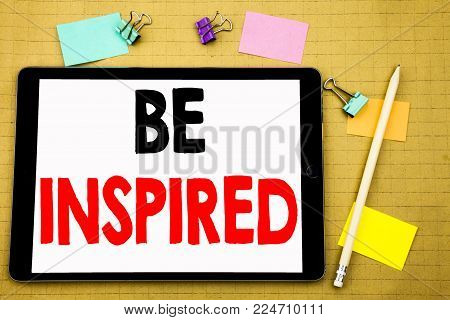 Hand writing text caption inspiration showing Be Inspired. Business concept for Inspiration and Motivation Written on tablet, wooden background with sticky note and pen
