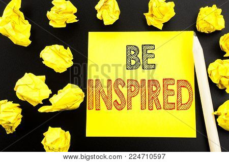 Handwritten text showing Be Inspired. Business concept writing for Inspiration and Motivation written on sticky note paper on black background. Folded yellow papers on the background