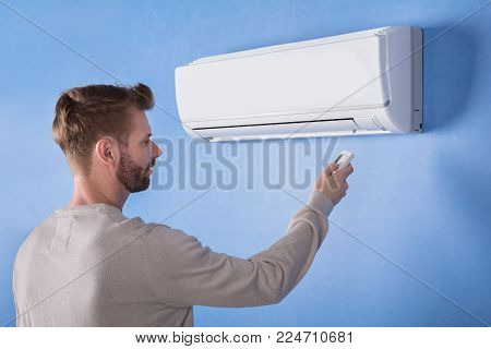 Rear View Of A Young Man Operating Air Conditioner Mounted On Blue Wall