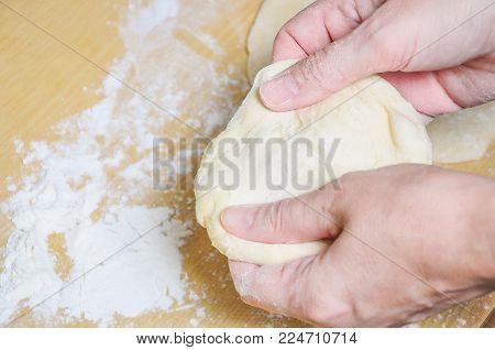 Woman doing manually the flat cake of leavened wheat dough