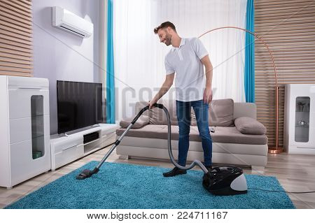 Young Man Cleaning Blue Carpet With Vacuum Cleaner At Home