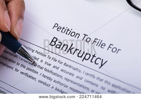 Close-up Of A Person's Hand Filling Bankruptcy Form poster