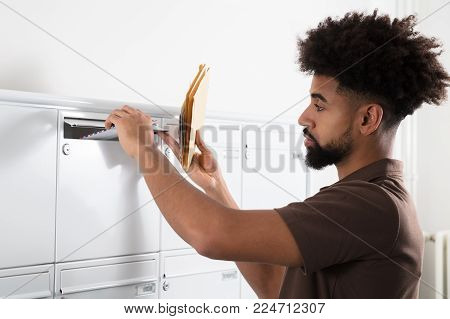 Side View Of A Young Man Putting Letters In Mailbox